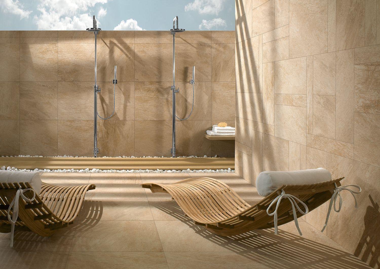 Wellnessbereich unter freien Himmel mit Fliesen in hellen Naturtönen auf Boden und an Wänden von Villeroy & Boch und zwei Holzliegen